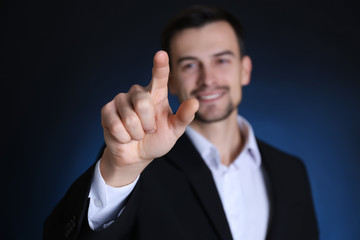 Handsome man in formal suit touching invisible screen on dark background