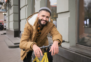 Attractive young hipster riding bicycle on city street