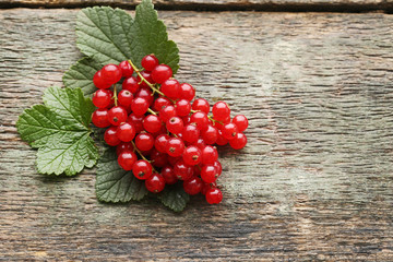 Red currants with green leafs on wooden table
