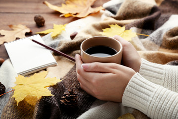 Female hands holding cup of coffee with plaid and notebook