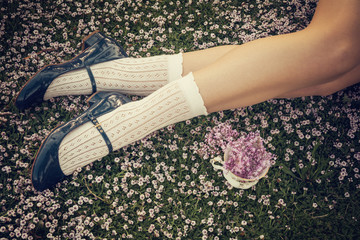 Girl legs lying on the grass with a fine bone china teacup and a bouquet of lilac flowers - Spring flowers - Shabby chic blossom