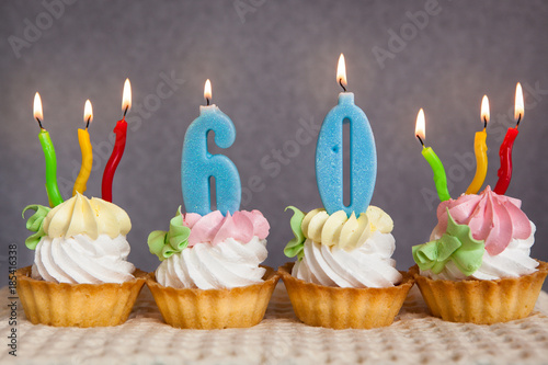Happy 60 Birthday Cakes And Blue Numbers Candles On Grey Background