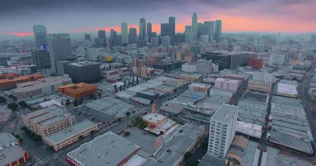 Fototapete - Flying forward to downtown Los Angeles skyline at sunset twilight dusk 4K aerial