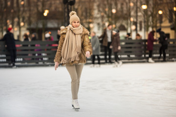 Full length portrait of young female with blonde hair in  fur coat, beige hat, scarf and trousers skating on ice rink, outdoors at winter / Weekends activities outdoor in cold weather/