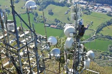 Antennen-Techniker bei der Reparatur hängt an einer Sendeanlage hoch über dem Abgrund (Lago Maggiore, Italien)