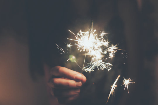 happy new year and merry christmas concept. hand holding burning sparkler firework bengal light. space for text. pyrotechnics concept, shining fire flame fireworks. happy holidays. toned