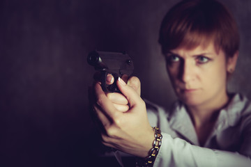 Woman with short hair aims a pistol.