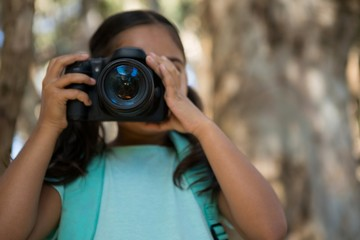 Little girl with backpack taking photos from dslr camera in the