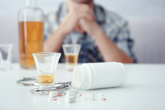Glass of alcohol, handcuffs and bottle with scattered drugs on table