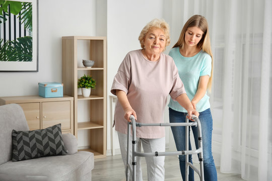 Young woman and her elderly grandmother with walking frame at home