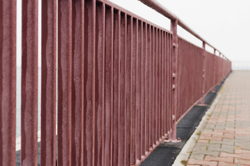 Red fence on the promenade in the sea