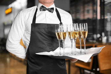 Waiter holding tray with glasses of champagne indoors