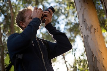 Man using dslr camera in the forest
