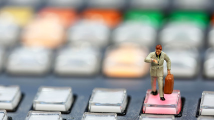 Miniature people : business man looking at watch and walk on the switcher control of Television Broadcast,color buttons