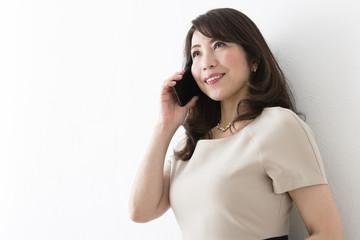 携帯電話で話すミドル女性