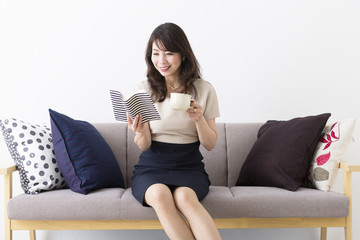 ソファに座って読書を楽しむミドル女性