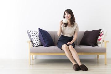 ソファに座ってくつろぐミドル女性