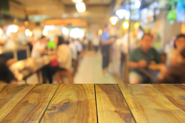 blurred wood table and people in food center with light bokeh. Wall mural