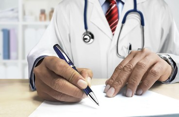 Doctor behind desk writing prescription for patient