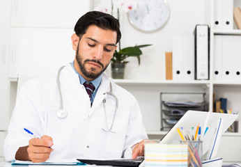 Doctor is working with documents in laptop