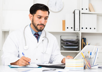 Young man doctor is working behind laptop and reading documents