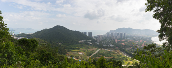 Evening panoramic view of nature with tropical plants and hills of Sanya city on Hainan Island