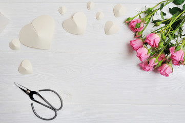 Mockup white origami hearts made of paper with pink roses and scissors, card for Valentine's Day. Flat lay, top view with a place for your text