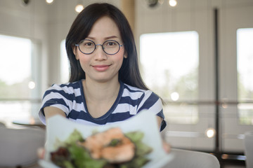 Closeup on Asian woman showing salmon salad.