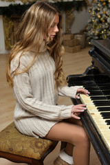girl teenager in a knitted sweater at a piano