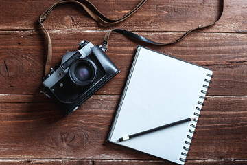 Retro photo camera with white note book on a stylish wooden background
