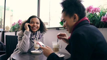 Two mixed race women sitting at the table in the street cafe using smartphone and talking