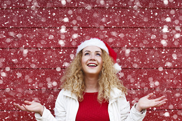 Cheerful young woman wear santa claus hat and looking up, christmas time new year holidays concept, copy space. Snowy effect, bulb snow