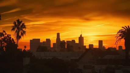Fototapete - Fiery sunrise over city of Los Angeles downtown skyline. 4K UHD Timelapse