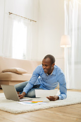 Doing project. Attractive gleeful afro-american man smiling and holding a paper and working on the laptop while sitting on the carpet on the floor