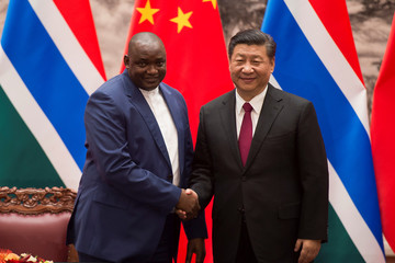 Gambian President Adama Barrow shakes hands with Chinese President Xi Jinping at the end of a signing ceremony at the Great Hall of the People in Beijing