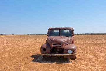 Rusty abandoned truck in arid landscape in Queensland