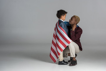 african american family wrapped in flag  on grey background