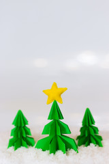 miniature paper pine tree figures with felted star on the top and red gift boxes, selective focus