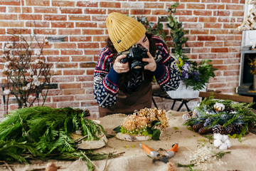 Woman taking photo of flower composition