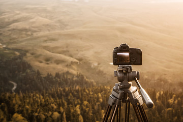 The camera on a tripod against the background of the mountains and the setting sun records video timelaps. Technology and travel.