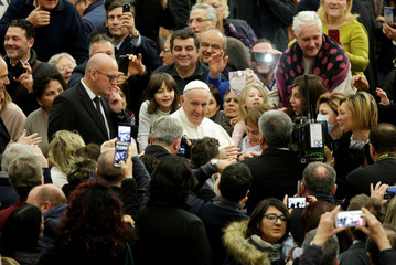 Pope Francis arrives to deliver Christmas wishes to Vatican staff during a special audience in Paul VI hall at the Vatican