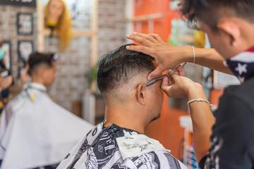 Barber haircut a customer at barbershop