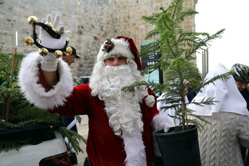 Israeli-Arab Issa Kassissieh, wearing a Santa Claus costume, holds a small tree and a bell during the annual Christmas tree distribution by the Jerusalem municipality in Jerusalem's Old City