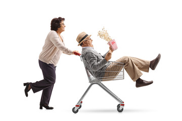 Elderly woman pushing a shopping cart with a mature man with a popcorn box riding inside