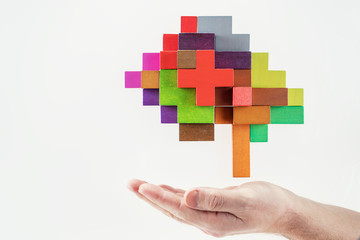 Human hand holding abstract brain. Human brain is made of multi-colored wooden blocks.