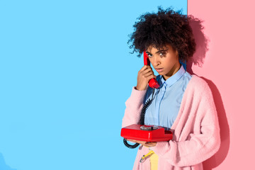 portrait of african american woman talking on retro telephone with pink and blue wall background