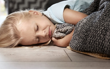 Helpless little girl crying on floor indoors. Child abuse concept