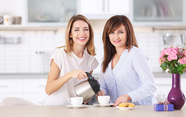 Attractive young woman drinking coffee with her mother at home