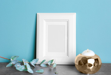Empty white frame, candle and eucalyptus branch on table near color wall