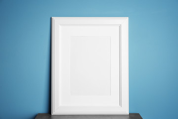 Empty white frame on table near color wall